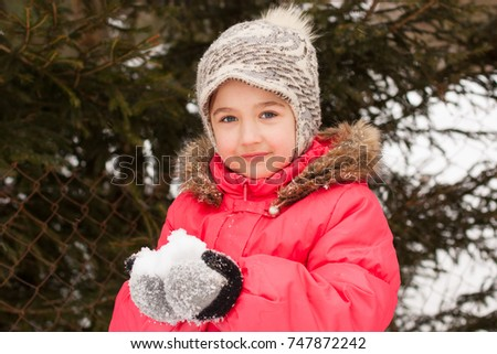 Portrait Of Cute Little Girl In Red Jacket Holding Fluffy Snow On Her Hands In Winter Park Outdoor Close Up. Child Walk. Playing With Snow.