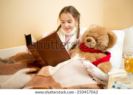 Portrait of cute little girl lying in bed and reading book to teddy bear - stock photo