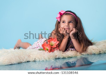 portrait of cute little girl on blue background - stock photo