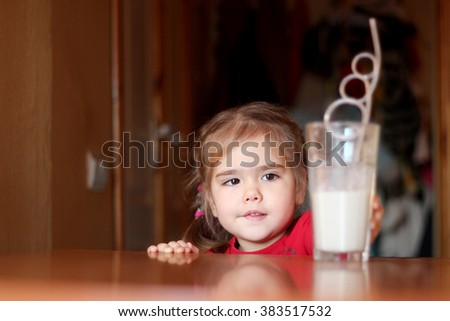Portrait of cute little girl reaching the glass of milk cocktail in a kitchen at home, food and drink concept, healthy food, indoor - stock photo