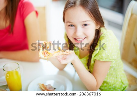 Portrait of cute little girl sitting by dinner table and eating pizza - stock photo