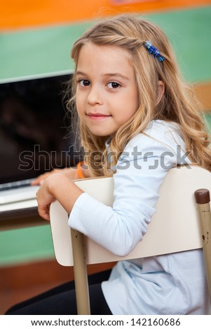 Portrait of cute little girl sitting on chair with laptop in classroom - stock photo