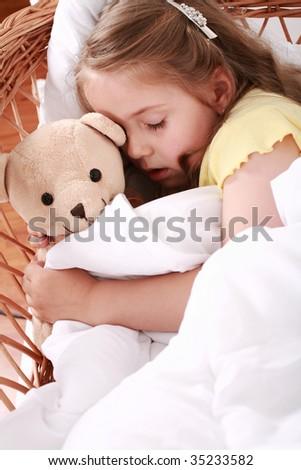 Portrait of cute little girl sleeping with teddy - stock photo