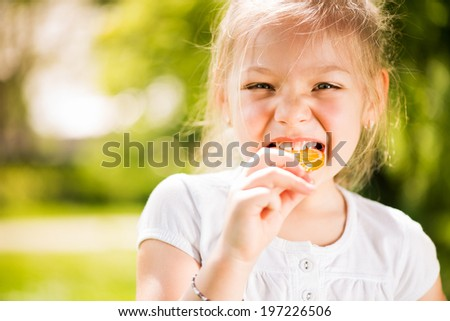 Portrait of Cute Little Girl Standing in the Park and holding in hand orange Lollipop. - stock photo