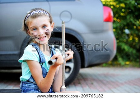 Portrait of cute little girl with dirty face helps her father to change wheel on their family car on warm day in the yard  - stock photo