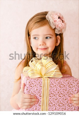 Portrait of cute little girl with gift box - stock photo