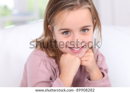 Portrait of cute little girl with hands on chin - stock photo