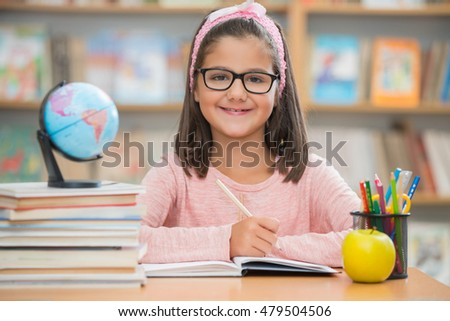 Portrait of cute little girl with sketch pen and paper at desk in class