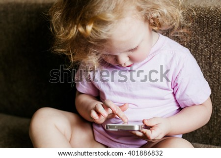 Portrait of cute little girl with the phone