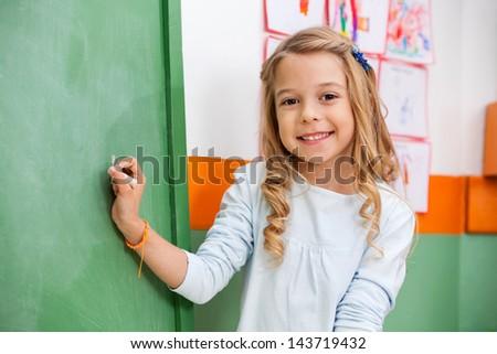 Portrait of cute little girl writing on board in kindergarten - stock photo