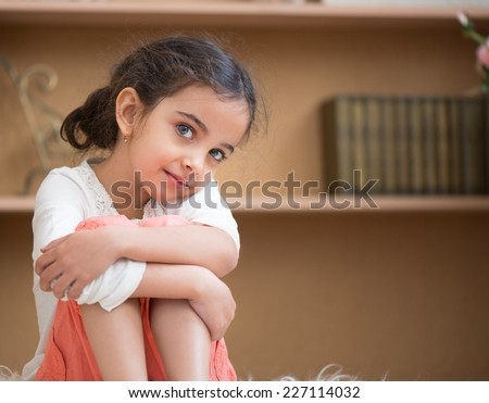 Portrait of cute little hispanic girl sitting on carpet at home - stock photo