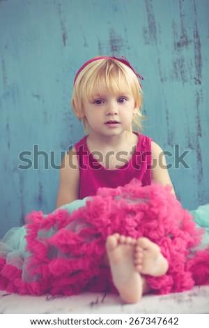 Portrait of cute little princess wearing beautiful tutu skirt on vintage wooden background - stock photo