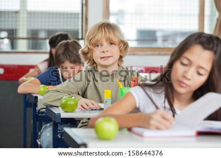 Portrait of cute little schoolboy sitting in a row with classmates at classroom - stock photo