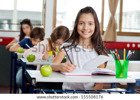 Portrait of cute little schoolgirl writing in book with classmates in background at classroom - stock photo