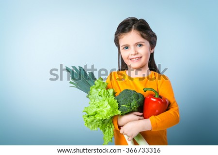 Portrait of cute little smiling girl. Girl looking at camera and holding fresh vegetables. Standing against grey background. Concept for healthy food - stock photo
