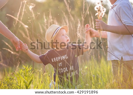 Portrait of cute little toddler boy in a straw hat holding his mother's  and brother's hands. Adorable child walking with his mom and sibling in the park on a sunny summer day. Family on sunset.  - stock photo