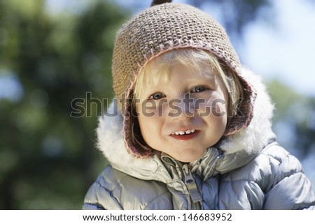 Portrait of cute little young girl in warm clothes smiling at yard - stock photo