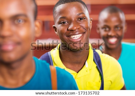 portrait of cute male african college student with friends - stock photo