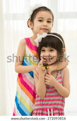 Portrait of cute mixed-race girl hugging her little sister