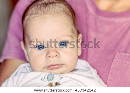 Portrait Of Cute 4-Month Newborn Baby Boy With Powerful Blue Eyes Lying On Father Arms - stock photo