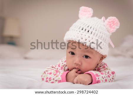 Portrait of cute newborn baby girl on the bed. - stock photo