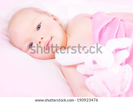 Portrait of cute newborn girl lying down in pink girly bedroom with rabbit soft toy, gentle little toddler, happy childhood concept - stock photo