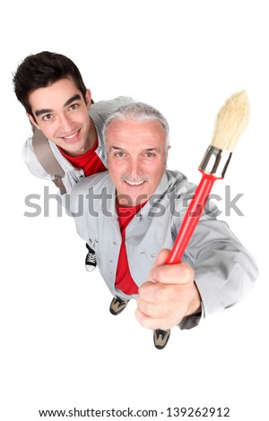 portrait of cute painter with senior instructor - stock photo