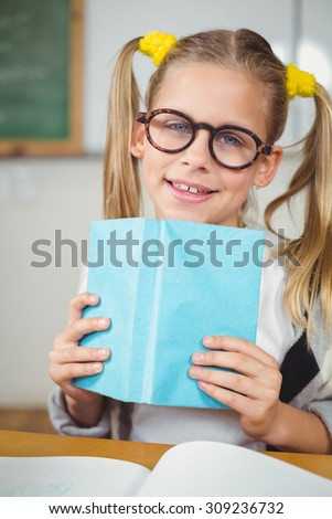 Portrait of cute pupil reading book in a classroom in school