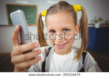 Portrait of cute pupil using smartphone in a classroom in school
