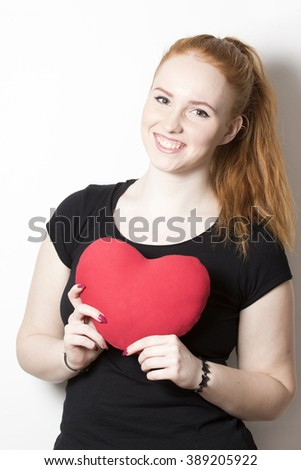 portrait of cute redheaded girl with a heart in her hand - stock photo