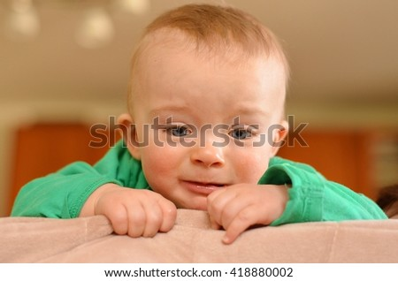 Portrait of cute sad baby with hands. Toddler  is upset he does not climb where he desired. - stock photo