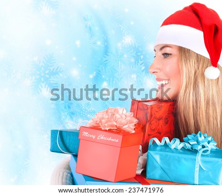 Portrait of cute Santa helper with many Christmas gifts in hands on blue snowflakes background, happy winter holidays concept - stock photo