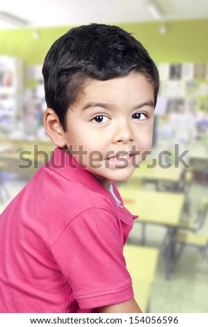 Portrait of cute schoolboy at workplace looking at camera  - stock photo