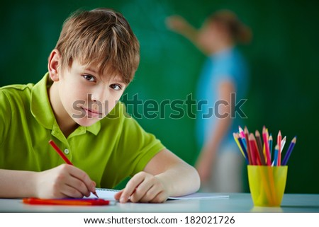 Portrait of cute schoolboy drawing with colorful pencils and looking at camera - stock photo
