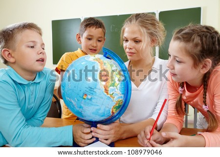 Portrait of cute schoolchildren and teacher looking at globe in classroom - stock photo