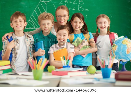 Portrait of cute schoolchildren and their teacher on background of blackboard - stock photo