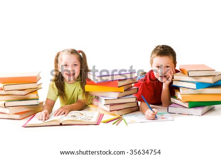 Portrait of cute schoolchildren looking at camera while reading book and drawing - stock photo