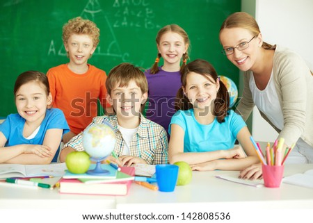 Portrait of cute schoolchildren looking at camera with their teacher and classmates on background