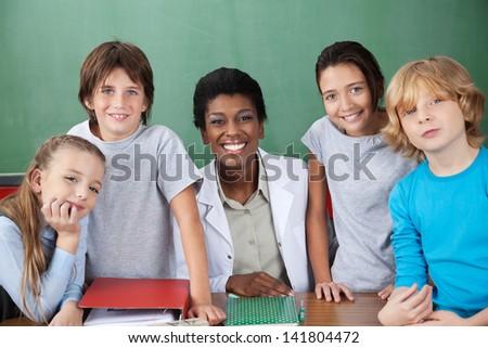 Portrait of cute schoolchildren with female teacher at desk in classroom - stock photo