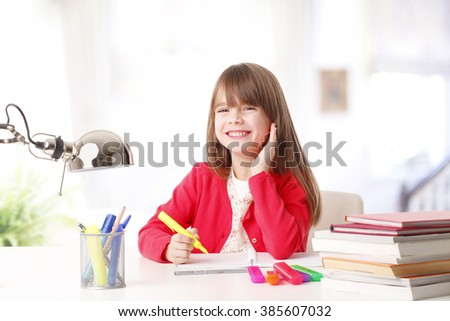 Portrait of cute schoolgirl drawing at desk at home while looking at camera and smiling.