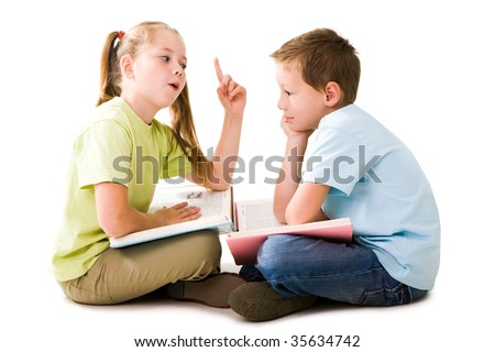 Portrait of cute schoolgirl explaining something to pensive lad who listening to her attentively - stock photo