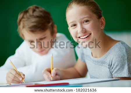 Portrait of cute schoolgirl looking at camera while drawing at lesson with her classmate on background - stock photo