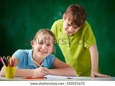 Portrait of cute schoolgirl looking at camera while drawing at lesson with her classmate standing near by - stock photo