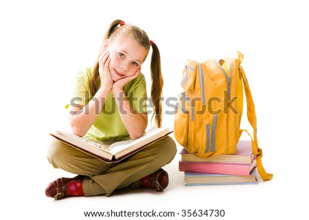 Portrait of cute schoolgirl with open book looking at camera over white background - stock photo
