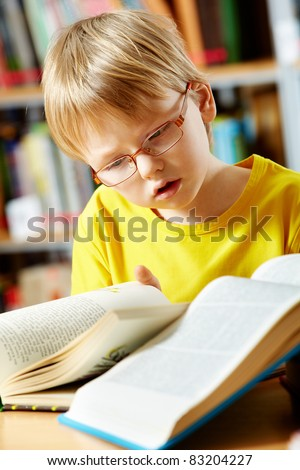 Portrait of cute schoolkid reading books in the library - stock photo