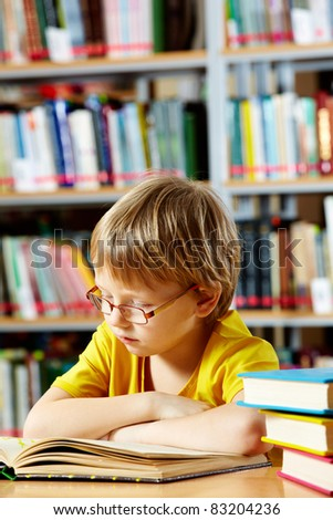 Portrait of cute schoolkid reading in the library - stock photo