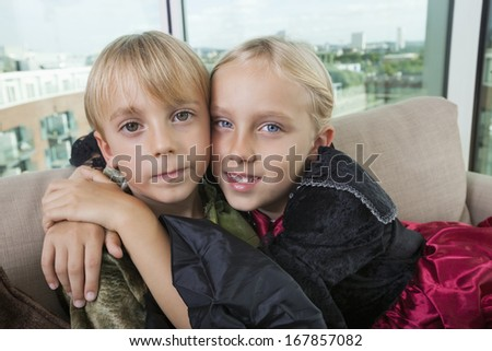 Portrait of cute siblings in dinosaur and vampire costumes at home - stock photo