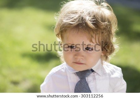 Portrait of cute small baby boy with blonde curly hair and round cheeks in white shirt with necktie standing on green grass yard looking away sunny day outdoor on natural background, horizontal photo - stock photo