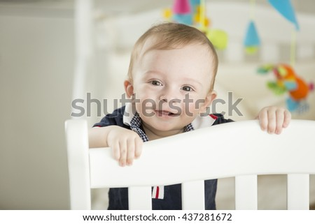 Portrait of cute smiling baby boy standing at his bed - stock photo
