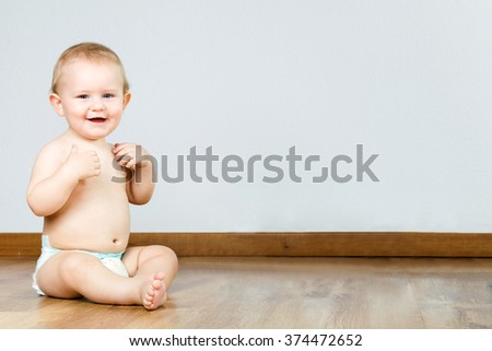 Portrait of cute smiling baby sitting at home.